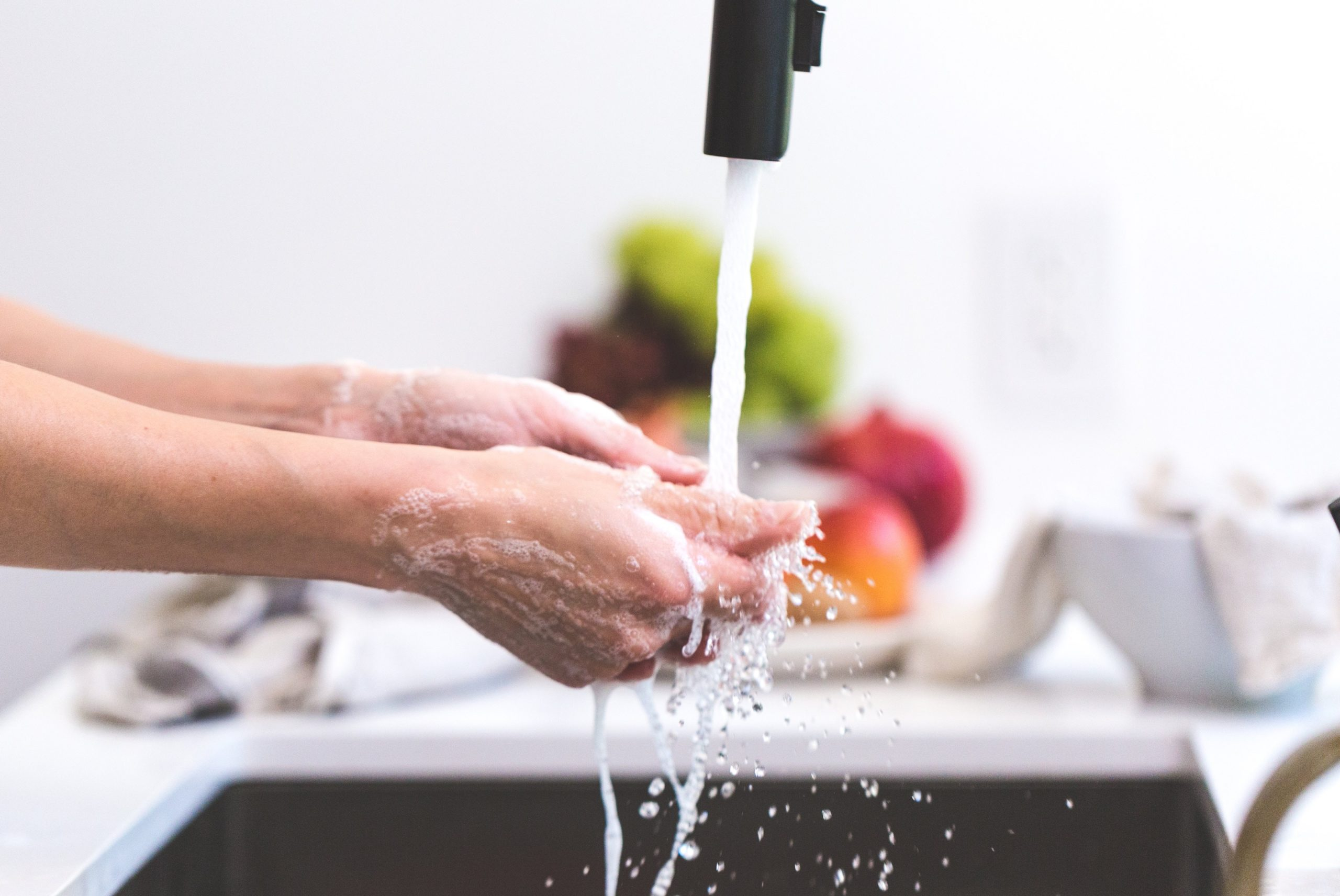 lady washing hands under tap, with colourful fruit in background
